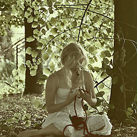 A young woman wearing a white summer dress holding a red heart sitting beneath a tree