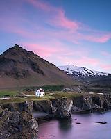Arnarstapi at sunrise, Mount Stapi and Snæfellsjökull glacier in background. Snæfellsnes Peninsula, West Iceland.