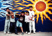 Smiling faces of kids on a street, with brightly painted sun wall mural in background, Ajijiic, Mexico