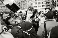 A father holds aloft his little girl during anti-government demonstrations in Cairo's Tahrir Square. The veiled woman in the foreground is wearing a head band with the Egyptian colors; the little girl is holding the Egyptian flag. (Cairo, Egypt - February 9, 2011)
