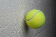 A tennis ball moving at 95 feet per second, or 28.95 meters per second is captured in flight just before it collides with a cinderblock wall. The tennis ball was launched from an air cannon as is commonly used to practice tennis.
