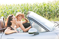 Happy friends enjoying road trip in convertible