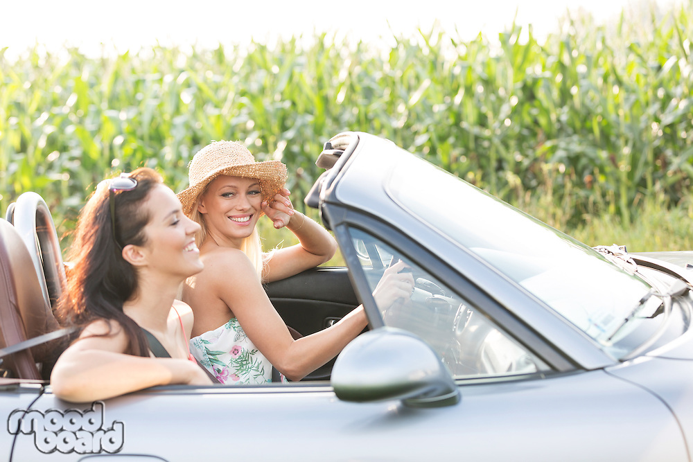 Happy friends enjoying road trip in convertible
