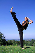 split kick - attractive young woman practicing self defense