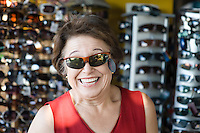 Senior woman trying on sunglasses, smiling