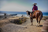 A horseback rider overlooks the U.S.-Mexico border wall at Friendship park in San Ysidro, California on Sunday, November 18, 2018.  The Central American migrant caravan trekking toward the United States converged on the US-Mexican border on November 15, 2018, after more than a month on the road, undeterred by President Donald Trump's deployment of thousands of American troops near the border.