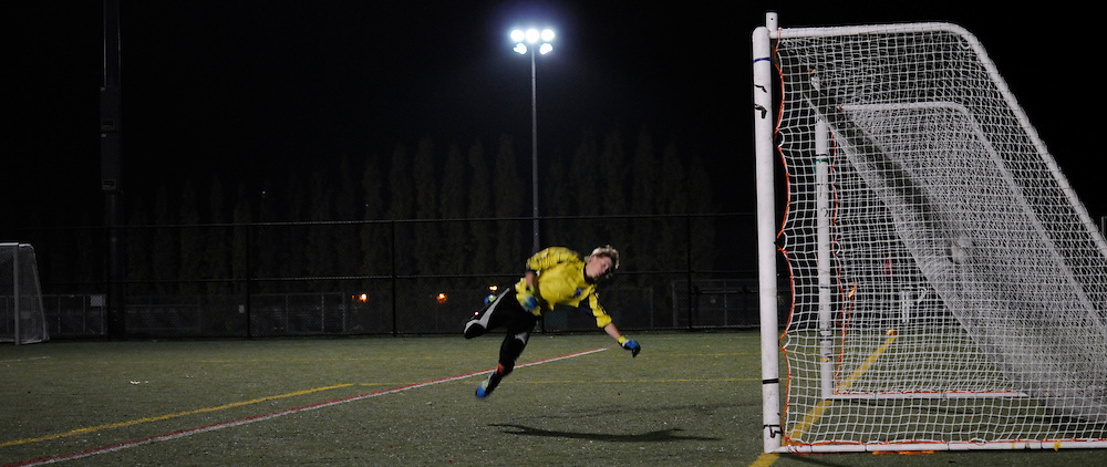 A soccer Goalkeeper misses the ball and is scored upon during an ametuer night time game. (Part of a series of 8 photographs)
