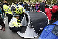 © Licensed to London News Pictures. 07/10/2019. London, UK. Police attempt to remove Extinction Rebellion protestors' tents from Millbank near Parliament in central London . Activists will converge on Westminster blockading roads in the area for at least two weeks calling on government departments to 'Tell the Truth' about what they are doing to tackle the Emergency. Photo credit: Peter Macdiarmid/LNP