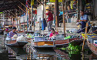 DAMNOEN SADUAK, THAILAND - CIRCA SEPTEMBER 2014: People and boats in the Damnoen Saduak floating market in the central region of Thailand.