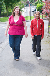 Mother and her teenaged daughter walking along the street together,