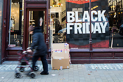 © Licensed to London News Pictures. 24/11/2017. Leeds, UK. Picture shows a shopper walking past a Black Friday sign in Leeds this morning on Black Friday. Photo credit: Andrew McCaren/LNP