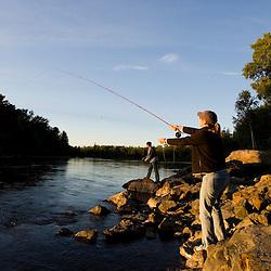 A couple fly-fishing on the Moose River below the dam on Brassua Lake in Rockwood, Maine.  Moosehead Lake region. (MR)