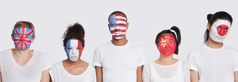 Portrait of multi-ethnic group with various national flags painted on face against white background