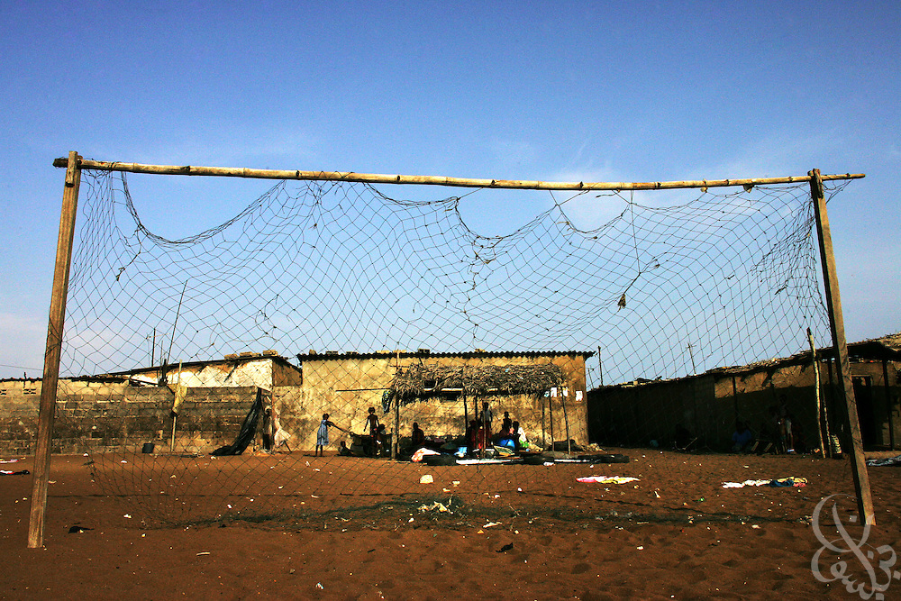 A poor slum in the Port Bouet neighborhood of Abidjan, Côte d'Ivoire is framed by a makeshift soccer goal February 17, 2006.  Many Ivorian parents and their children view football as a potential way out of poverty.