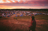 """Susan Leopold, a member of the Patawomeck tribe of Virginia, watches the sun rise over an encampment where thousands have come to protest. """"Never in my lifetime did I think I would bare witness to a gathering of indigenous people speaking such diverse languages who have come together to stand united for the one thing we all so deeply care about,"""" she said."""