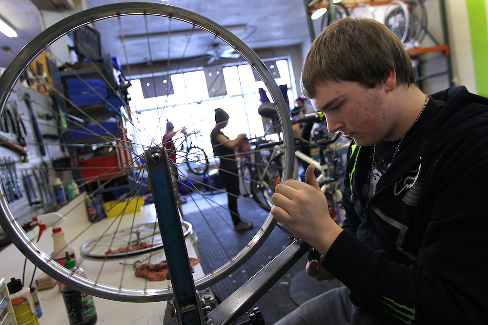 Youth Express apprentice Marcus Wachholz, 17, works to straighten wheels on a donated bike at Express Bike Shop in St. Paul, Minnesota.  By refurbishing and selling bicycles, youth apprentices learn mechanical, business, and entrepreneurial skills..