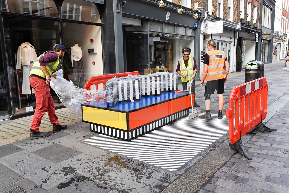 """© Licensed to London News Pictures. 12/09/2019. LONDON, UK.  Workmen begin the installation of """"Walala Lounge"""", designed by artist and designer Camille Walala.  South Molton Street in Mayfair will be transformed into an urban living room.  10 sculptural benches, accompanied by planters and a series of oversized flags strung, bunting-style, from shopfront to shopfront, will convert the street into an immersive corridor of colour as part of this year's London Design Festival.  Photo credit: Stephen Chung/LNP"""