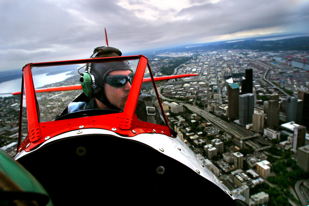 Pilot Jayson S. Wilson looks out over downtown Seattle as the Red Baron Pizza Squadron biplane pilots prepare for the SeaFair airshow. Questionable weather on this day prevented the squadron from performing their usual stunt routine.
