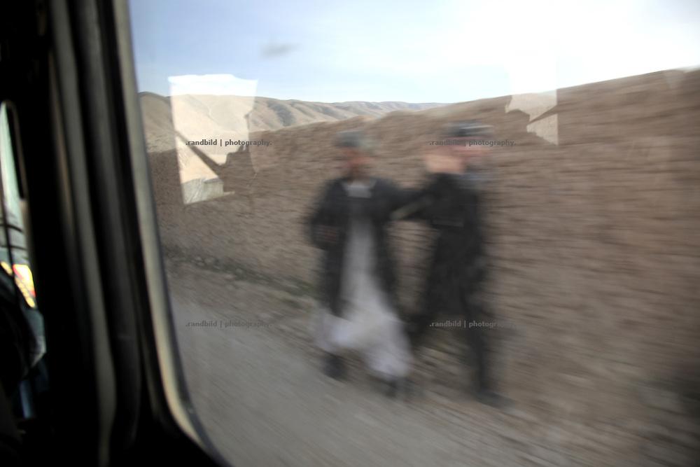 Two afghan men passes a german military convoy near Maza- e Sharif.