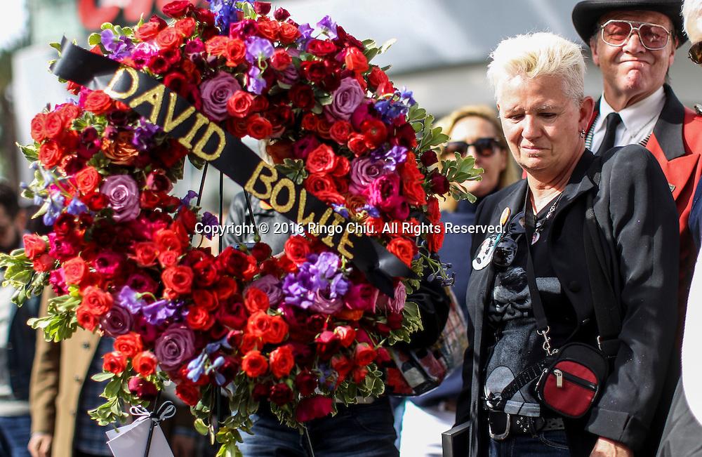 1月11日,在美国洛杉矶,歌迷将鲜花、蜡烛和留有文字的纸条放置在好莱坞星光大道大卫&middot;鲍伊(David Bowie)的星旁。英国传奇歌手大卫鲍伊与病魔抗争18个月后今天病逝,享寿69岁。新华社发 (赵汉荣摄)<br /> People stand near a wreath at the Hollywood Walk of Fame star of David Bowie in Los Angeles, Monday, Jan. 11, 2016. Bowie, the other-worldly musician who broke pop and rock boundaries with his creative musicianship, nonconformity, striking visuals and a genre-spanning persona he christened Ziggy Stardust, died of cancer Sunday. He was 69 and had just released a new album. (Xinhua/Zhao Hanrong)(Photo by Ringo Chiu/PHOTOFORMULA.com)<br /> <br /> Usage Notes: This content is intended for editorial use only. For other uses, additional clearances may be required.