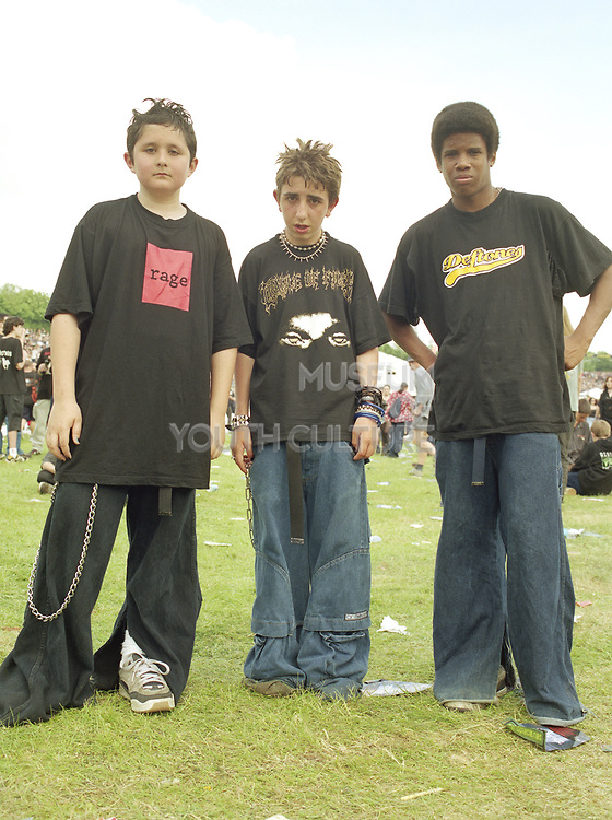 Three young men standing slouched forward in the middle of a music festival