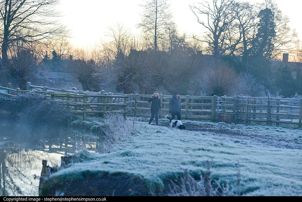 © Licensed to London News Pictures. 29/12/2013. East Bergholt, UK. A man an woman walk a dog at Flatford Mill. Early morning frost and mist on the River Stour at Deadham Vale this morning 29th December 2013. Photo credit : Stephen Simpson/LNP