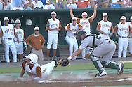 Nick Peoples (L) of Texas slides past Tulane catcher Greg Dini (R) for the first Longhorn run in the bottom of the first inning.  Texas defeated Tulane 5-0 in the second round of the College World Series at Rosenblatt Stadium in Omaha, Nebraska on June 20, 2005.