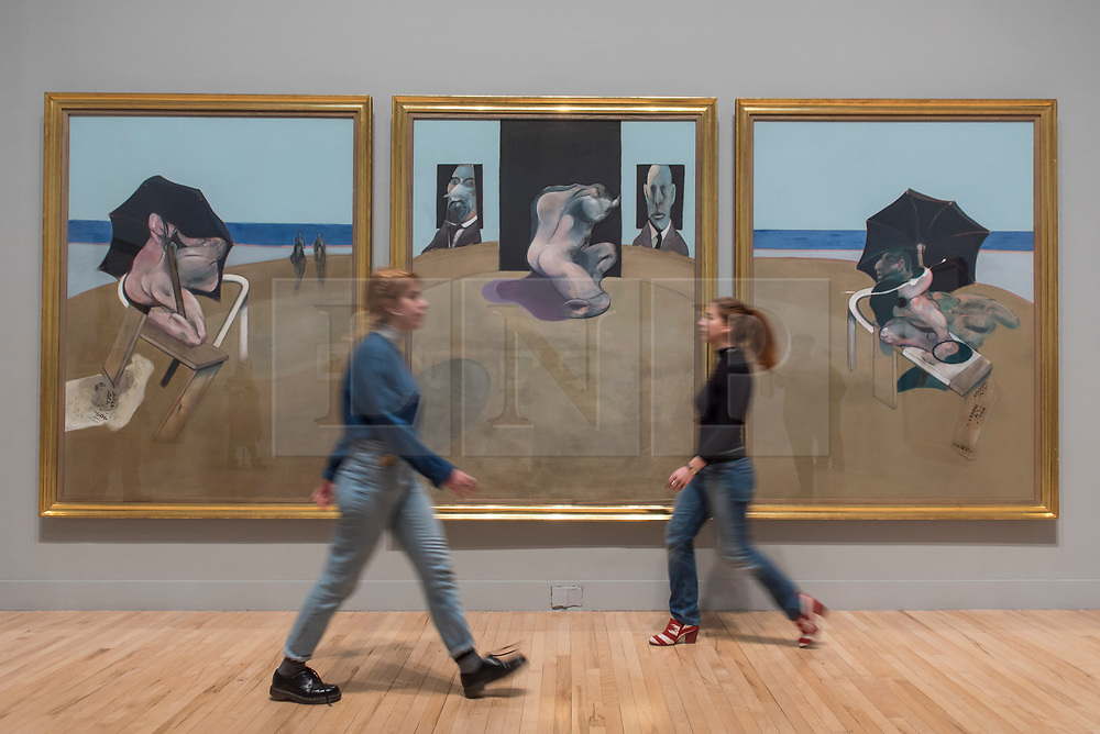 "© Licensed to London News Pictures. 26/02/2018. LONDON, UK. Staff members walk in front of ""Triptych"", 1974-1977, by Francis Bacon.  Preview of ""All Too Human"", an exhibition at Tate Britain which explores how artists in Britain have stretched the possibilities of paint in order to capture life around them.  The exhibition runs 28 February to 27 August 2018 and includes rarely seen works by Lucian Freud and Francis Bacon.  Photo credit: Stephen Chung/LNP"