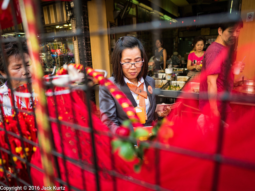 "03 FEBRUARY 2016 - BANGKOK, THAILAND:  A woman shops for Chinese New Year mementos before Chinese New Year in Bangkok. Thailand has the largest overseas Chinese population in the world; about 14 percent of Thais are of Chinese ancestry and some Chinese holidays, especially Chinese New Year, are widely celebrated in Thailand. Chinese New Year, also called Lunar New Year or Tet (in Vietnamese communities) starts Monday February 8. The coming year will be the ""Year of the Monkey.""            PHOTO BY JACK KURTZ"