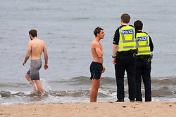 Portobello, Edinburgh, Scotland, UK. 5 April, 2020. On the second Sunday of the coronavirus lockdown in the UK the public are outside taking their daily exercise. Pictured. Police talk to men in swimming trunks on beach at Portobello. After discussion the men were allowed to continue with their swim. Iain Masterton/Alamy Live News