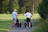 Teenage boys walk along the golf path at Nicklaus North Golf Course in Whistler, BC Canada.
