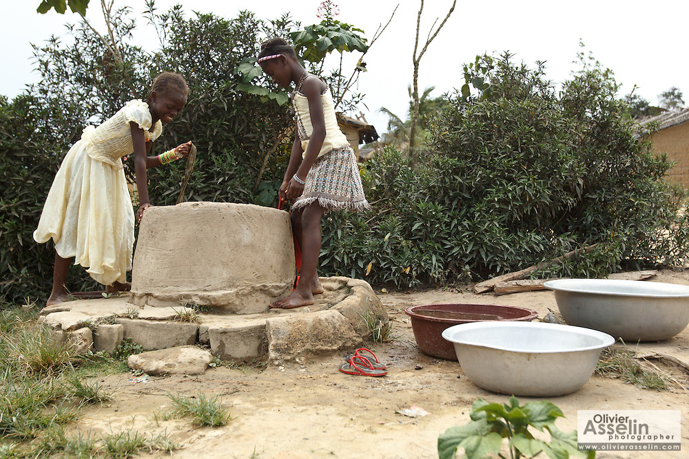 Two girls draw water from a well in the village of Popoko, Bas-Sassandra region, Cote d'Ivoire, on Sunday March 4, 2012.