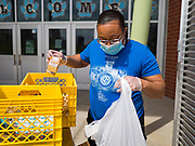 22 APRIL 2020 - DES MOINES, IOWA: SIMONA LEWIS packs milk into grab and go lunches at Edmunds Elementary School. Schools in Iowa are closed for the rest of the school year because of the COVID-19 (Coronavirus/SAR-CoV-2) pandemic. Des Moines Public Schools expanded their school lunch and distance learning efforts this week. Lunches are being distributed at all of the district's elementary and middle schools and officials have started distributing computers so students can participate in distance learning. The meal distribution was done according to social distancing guidelines.          PHOTO BY JACK KURTZ