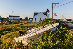 A motorboat in a rose bush in front of Alley's Bay Advent Christian Church in Beals, Maine.