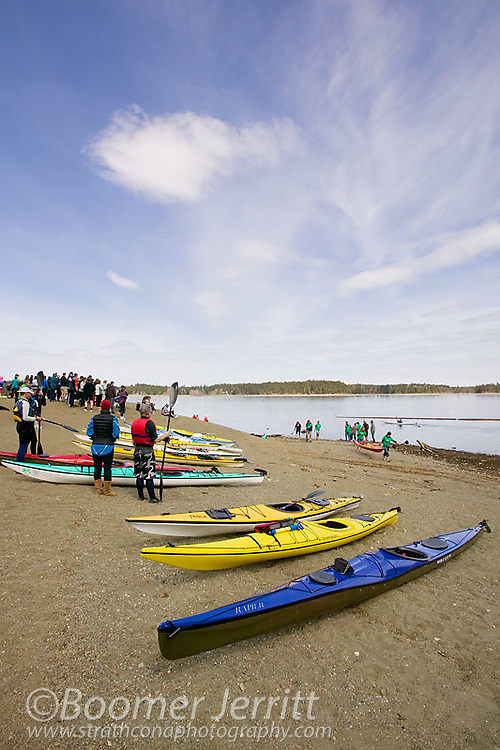 Kayaks line the beach at Comox Lake during the annual snow to surf relay in the Comox Valley.  Comox Valley, Vancouver Island, British Columbia, Canada.