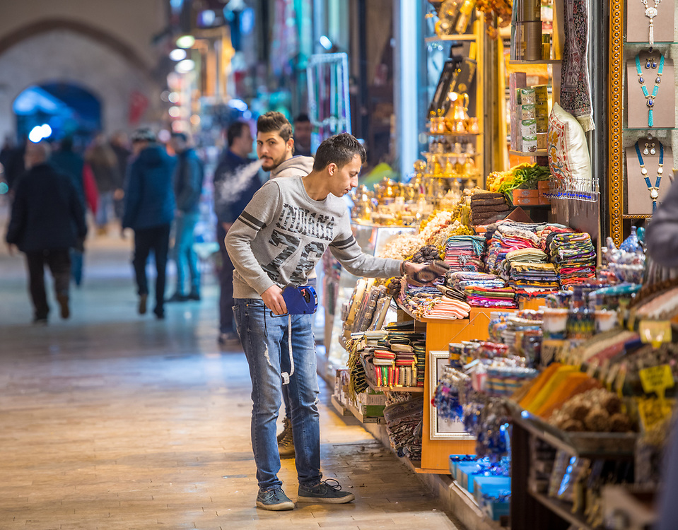 Young adult male using tagging label gun to put price tags on various goods for sale on merchant stall in Istanbul Spice bazaar in Turkey