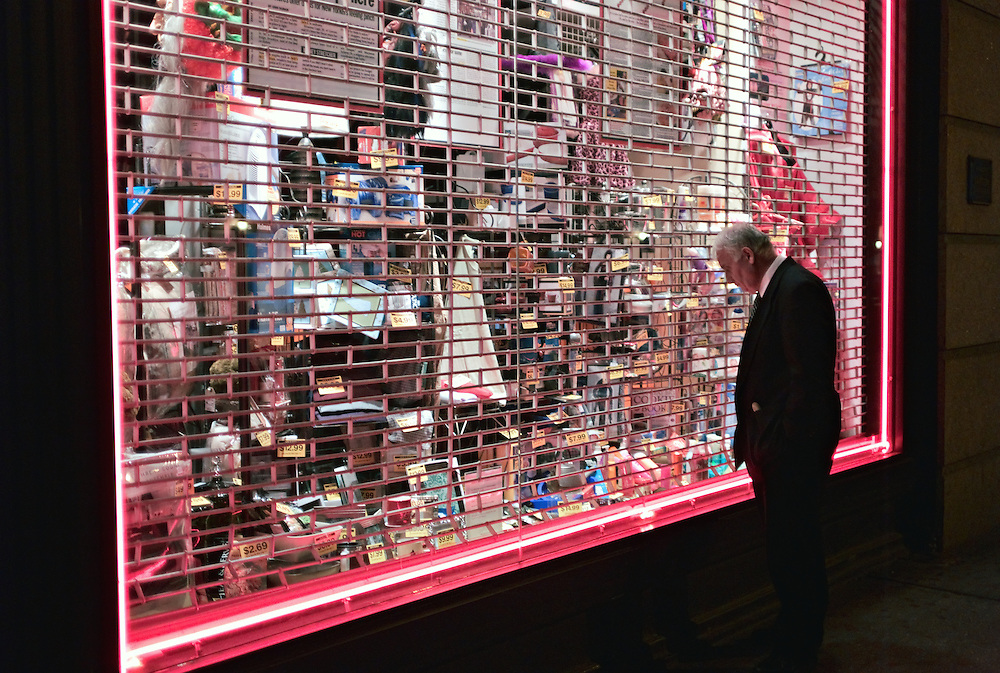Gray-haried man in suit looking at storefront window at night, New York, US