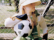 Young lady gazes into the distance holding a football, dressed in sportswear.