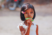 A young girl walks with a green candy ice in Burma (Myanmar)
