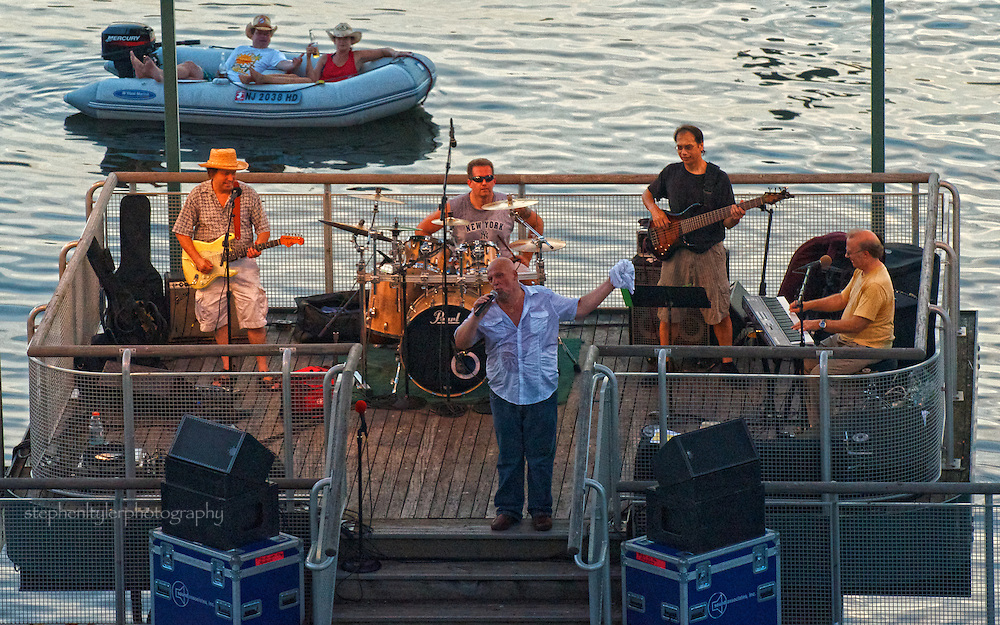 Tommy a/k/a The Blues Buddha, performing at the Jazz & Blues @ Dusk Friday night Summer music series on the Yonkers pier in 100+ degree heat as part of the crowd floats by behind the stage..