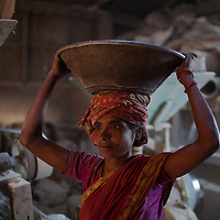 A women carries corn on her head in a corn mill in the docks of Chittagong in Bangladesh.
