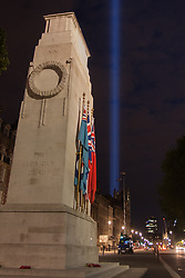 London, August 4th 2014.The Cenotaph remains illuminated as a  shaft of light rises from behind the Houses of Parliament, as Britain remembers the outbreak of World War 1 a century ago.