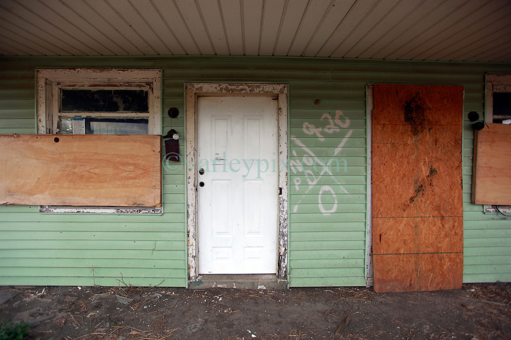 27 August 2014. Lower 9th Ward, New Orleans, Louisiana.<br /> Hurricane Katrina 9 years later. Many derelict, falling down buildings dot the landscape as the area continues to struggle with recovery from Hurricane Katrina. The universal code spray painted outside the front door by search and rescue teams remains as it was almost 9 years ago. The building was searched by NOPD with 0 victims discovered inside.<br /> Photo; Charlie Varley/varleypix.com