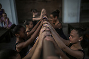 Students of the Manguinhos community ballet stretch  prior a  ballet class outside a public library in Manguinhos neighbourhood, Rio de Janeiro, Brazil, Monday, June 11, 2018. The Manguinhos community ballet has been a reprieve from the violence and poverty that afflicts its namesake neighborhood for hundreds of girls who have benefitted from free dance classes since 2012. (Dado Galdieri for The New York Times)