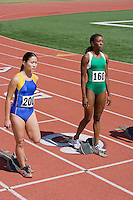 Female athletes next to starting blocks, ready to run