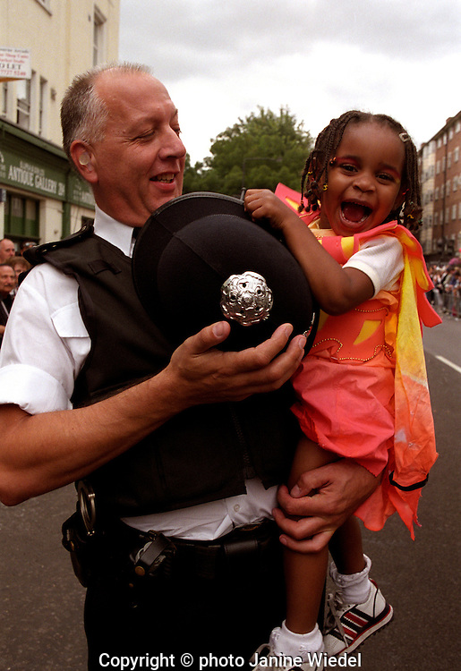 A police officer carrying  a small girl at the notting Hill carnival in London.