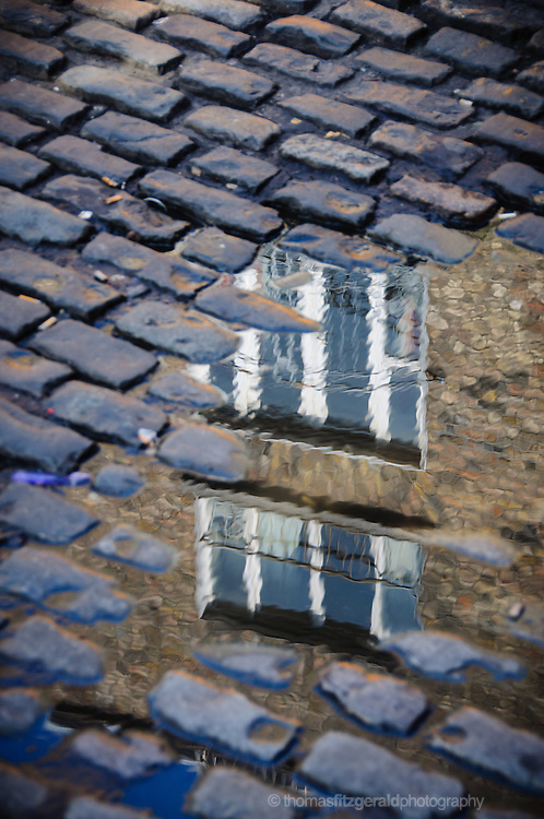 The refelctions of a sety of windows in the puddle among some coble stones