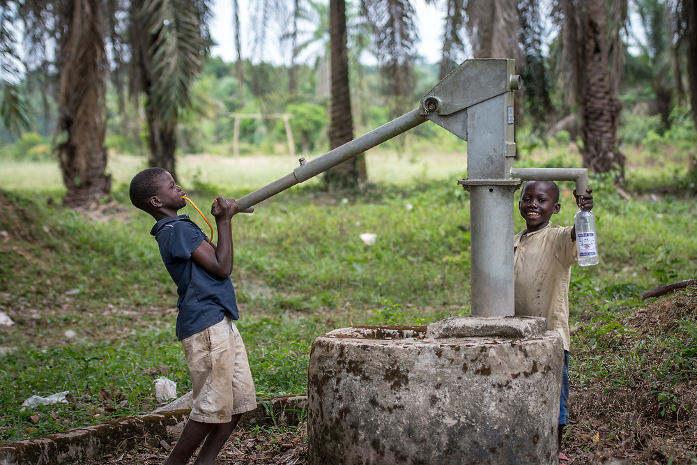 Young children pump water from a well in Ganta, Liberia