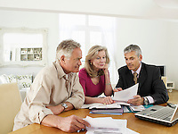 Senior couple sitting at table with financial advisor