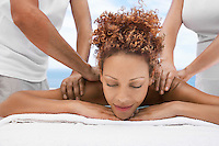 Woman receiving massage from two people head and shoulders eyes closed